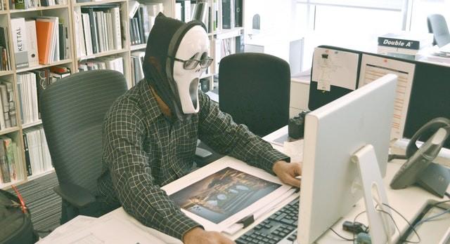 Persona utilizando ordenador con máscara de Scream
